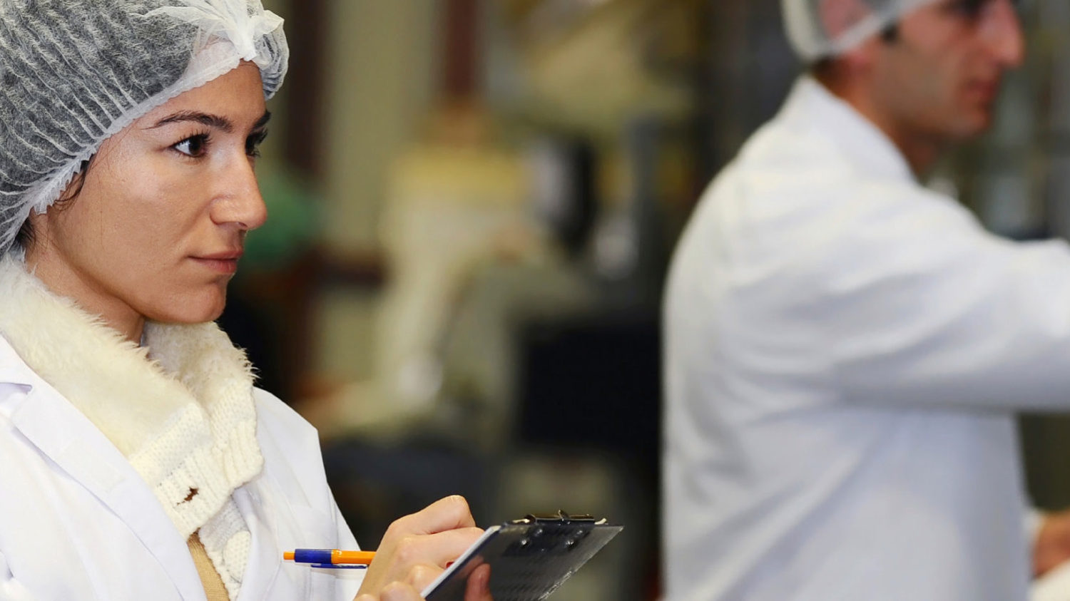 Workers in lab coats and hair nets take notes on clipboards