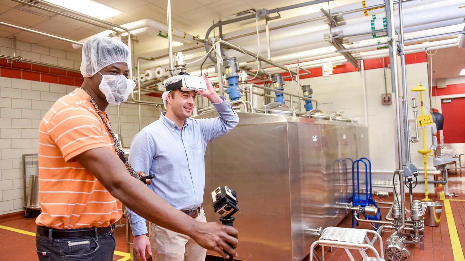 Two men operate VR equipment in a food processing facility.