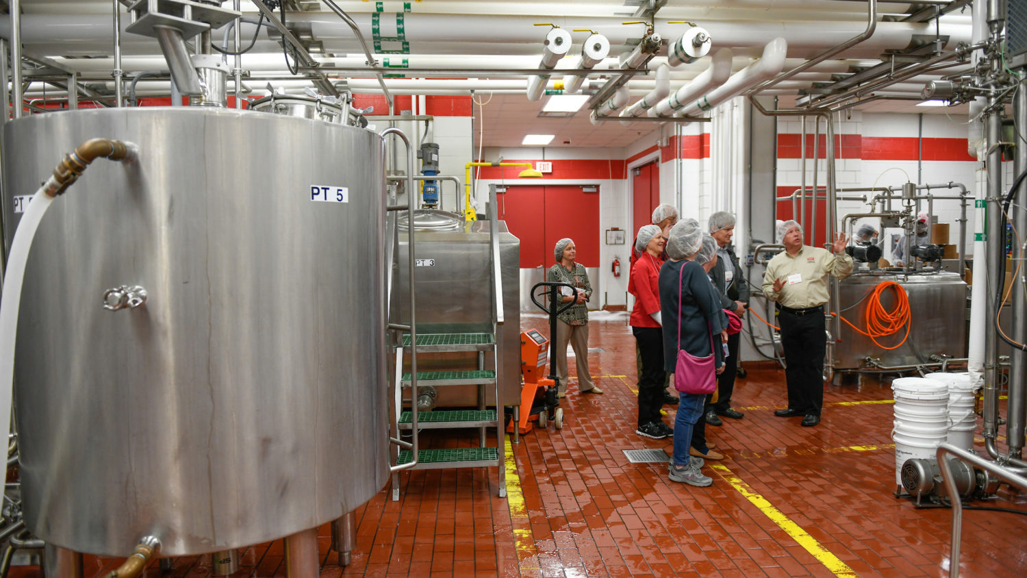 Group of people wearing hair nets tour a dairy production facility.