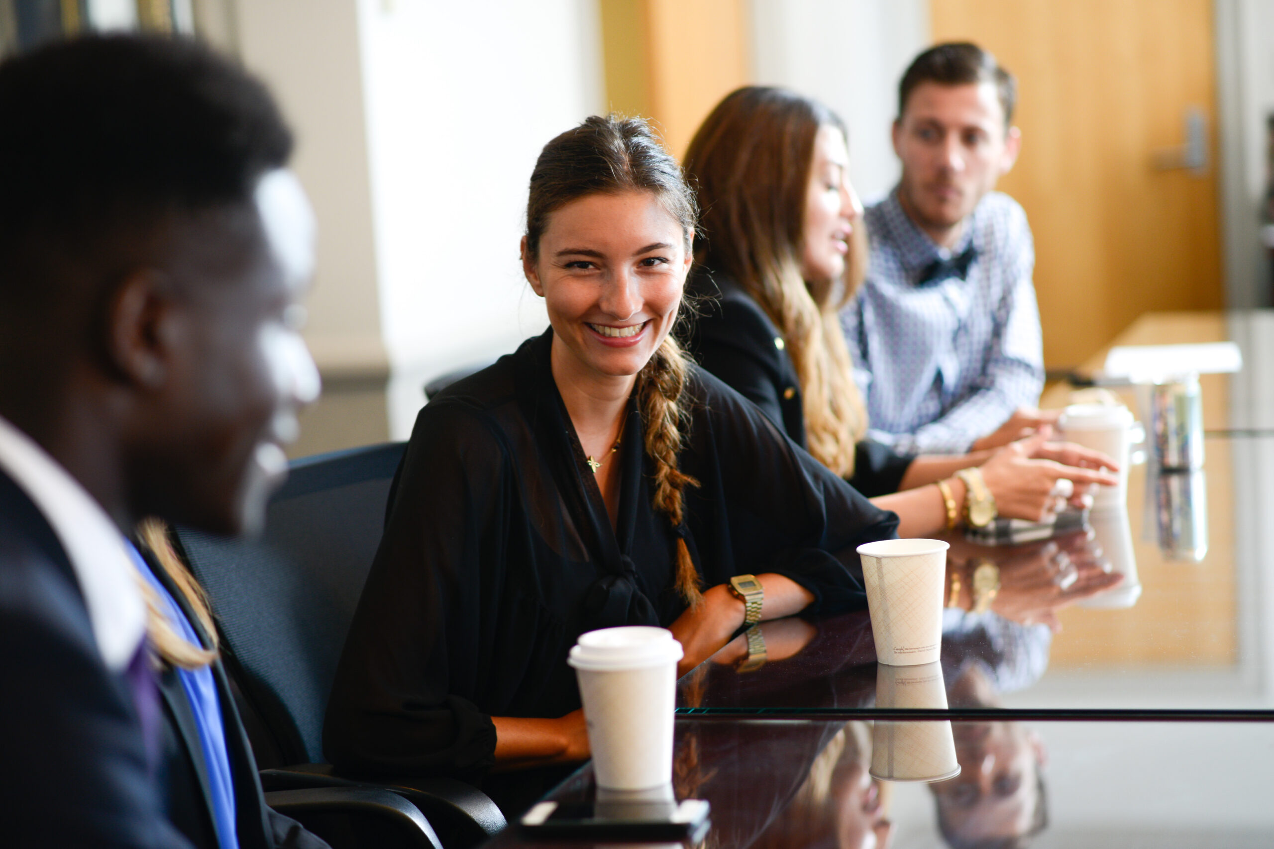 Header for Internship Page and Serves as a link to the Career Page - Student smiling at conference table